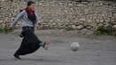 A young student enjoying kicking the football.