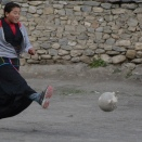 A young student enjoying kicking the football.